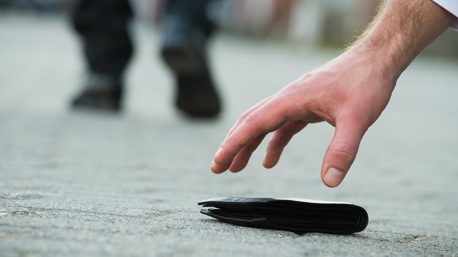 Hand, die nach Portemonnaie greift
